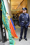 March 16, 2013 - New York, NY, U.S. - Police Officer wearing chest holster to carry large flag as he stands snext to Emerald Society flag and other flags, shortly before he marches in the 252nd annual NYC St. Patrick's Day Parade.