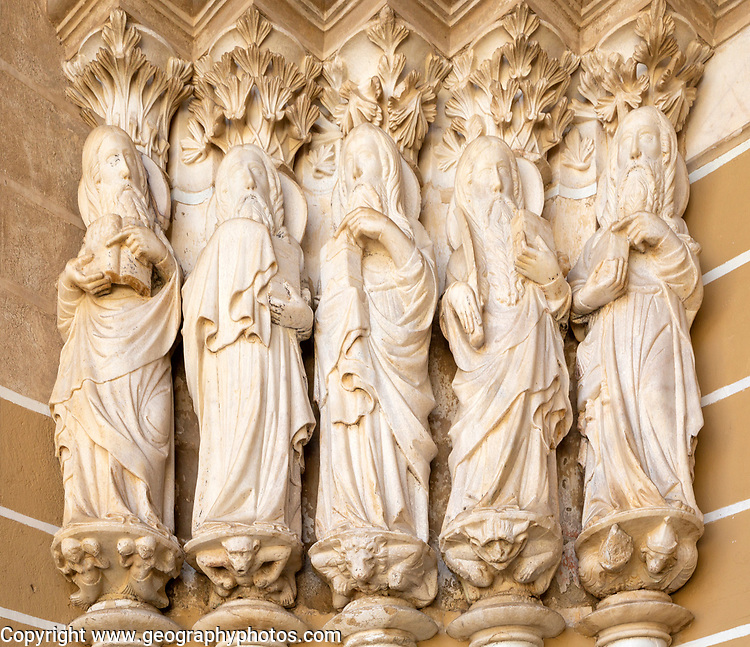 Historic Roman Catholic cathedral church of Évora, Sé de Évora, in the city centre, Basilica Cathedral of Our Lady of Assumption. This image shows details of the carved Gothic period Apostles in the main doorway entrance. Marble columns are occupied by huge statues of the Apostles dating from the 1330s.