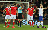 Aleksandar Katai of Serbia (R) protests for receiving a yellow card by match referee Alberto Mallenco (C) during the 2018 FIFA World Cup Qualifier between Wales and Serbia at the Cardiff City Stadium, Wales, UK. Saturday 12 November 2016