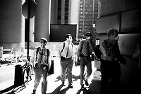 Workers arrive in Lower Manhattan past the Federal Reserve on their first look since the WTC attacks. Many work protective masks because of dust, odor and contaminants from the fire. September 17, 2001