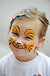A young blonde girl with her face painted in cat or tiger stripes smiles.