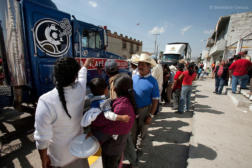 "2 may 2009 - La Gloria, Mexico - Residents of La Gloria, a farming village in the Mexican state of Veracruz, line up outside a truck giving out free coffee. The local government has also started giving everybody in town three free meals a day. But according to the activists, they don't need food. They need regulation to decrease the amount of contamination in their communities. In Mexico, local government is known to be astoundingly corrupt. Located in the states of Veracruz and Puebla, near Mexico City, Granjas Carroll is an industrial pig farms that produces close to 1 million animals a year. It is 50% owned by US company Smithfield Foods, the worlds largest producer and processor of pork products. In La Gloria, near where the farms are located, residents have been complaining about manure dumps, flies and smell from the farms for a long time. Since February, they have warned the authorities that the wastes of these pig breeding farms caused an outbreak of respiratory infections and pneumonia in 60% of their 3000 inhabitants. Mexican media has called the Carrol pig farms ""ground zero"" for infection. It recently was confirmed that an influenza case in the city, reported two weeks before the cases in Mexico City, was in fact the new strain of H1N1, combining genetic material from avian, swine and human influenza. The Food and Agriculture Organization (FAO) says that so far there is no established evidence that this strain of the influenza A virus has entered the human population directly from pigs, but it urges national governments and the international community to step up disease surveillance in swine. FAO together with the World Organization for Animal Health (OIE), will send a team of experts to Mexico this week to help the government assess the epidemiologic situation in the pig production sector. A spokesperson from Smithfields Foods said there is no clinical signs of influenza being reported in pigs or employees in the farm. Photo credit: Benedicte Desrus / S"