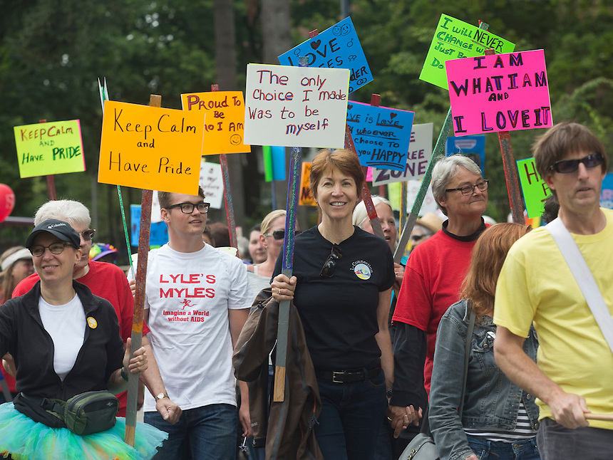 """Participants walk and hold signs at the """"Dyke March"""" part of the Pride event Esther Short Park in downtown Vancouver Sunday July 9, 2016. he annual Saturday in the Park Pride event celebrates the local gay, lesbian, bisexual and transgender community. (Photo by Natalie Behring/ for the The Columbian)"""