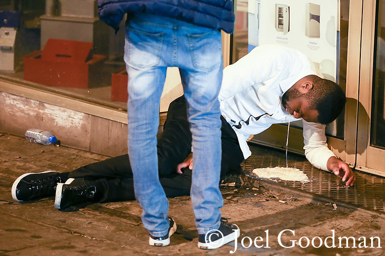 © Joel Goodman - 07973 332324 . No syndication permitted . 01/01/2014 . Manchester , UK . A man vomits in a doorway , on Withy Grove in central Manchester . Revellers see in the New Year in Manchester today (January 1st 2014) as police report that officers are at full stretch responding to calls . Photo credit : Joel Goodman