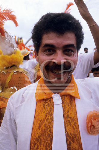 Rio de Janeiro, Brazil. Carnival: samba school man in orange lace shirt and white suit and tie.