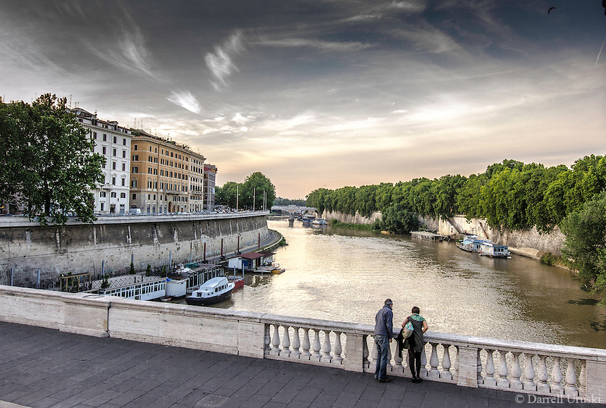 Fine Art Landscape Print Photograph. A romantic river scene of the Tiber river in the ancient city of Rome. The lighting of the day reveals the subtle textures of the river water, and the historical building that gracefully line the fortified walls of the river shoreline.