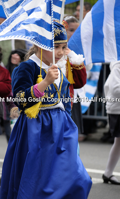 Greek Parade in New York City. A girl in a costume carries a Greek flag in the Greek Parade in New York City.