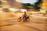 VIETNAM, Hanoi, a man rides his moped through and intersection at night