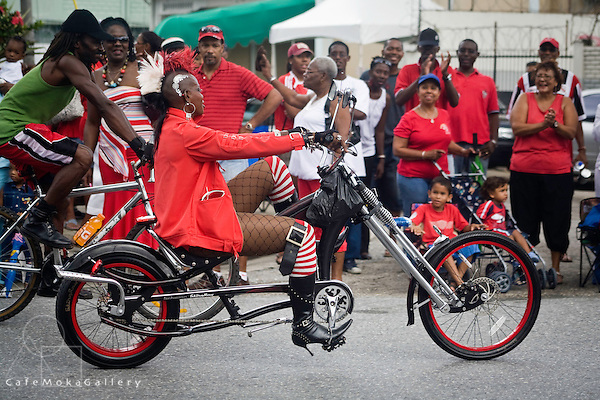 Eccentric woman cyclist in national Colours in the Independence day parade, Port of Spain
