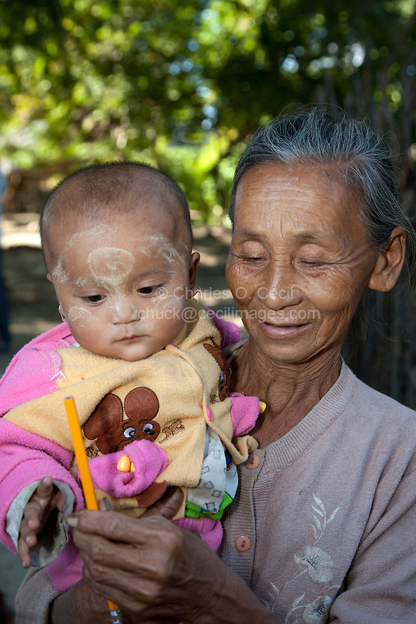 Myanmar, Burma.  Village Grandmother Holding Grandchild with New Pencil.  The child has thanaka paste on her face, a cosmetic sunscreen.  Burman (Bamar) ethnic group.