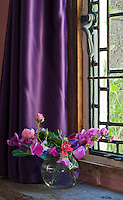 The deep violet curtains of the small leaded living room window are the perfect foil for a bouquet of garden flowers in a simple glass vase