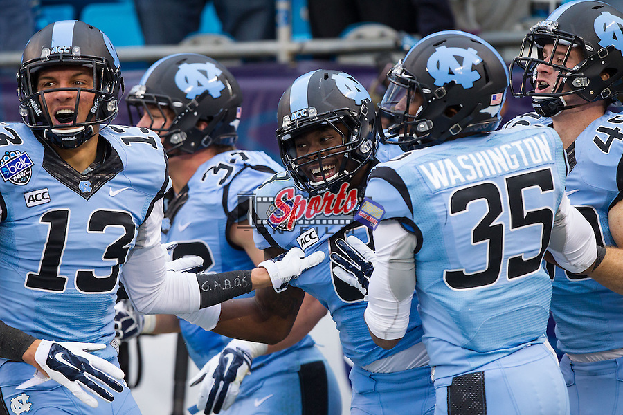 T.J. Logan (8) of the North Carolina Tar Heels celebrates with teammates after returning a kick-off 78 yards for a touchdown against the Cincinnati Bearcats during the Belk Bowl at Bank of America Stadium on December 28, 2013 in Charlotte, North Carolina.  The Tar Heels defeated the Bearcats 39-17.   (Brian Westerholt/Sports On Film)