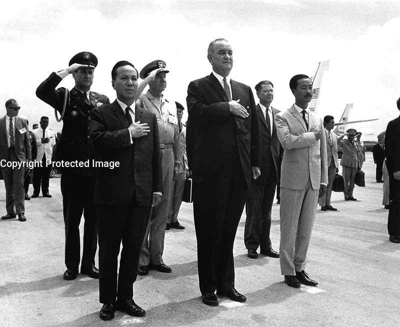Chairman Nguyen Van Thieu, President Lyndon B. Johnson and Prime Minister Nguyen Cau Ky salute during the playing of the U.S. and Vietnamese National Anthems during welcoming ceremonies at Guam's International Airport, Agana, March 20, 1967. (USIA)<br /> NARA FILE #:  306-SSM-8K-2<br /> WAR &amp; CONFLICT BOOK #:  388