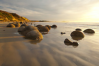 Multiple Moeraki Boulders | golden morning sun light | Sand ripples | cloudy sky | Coastal Otago