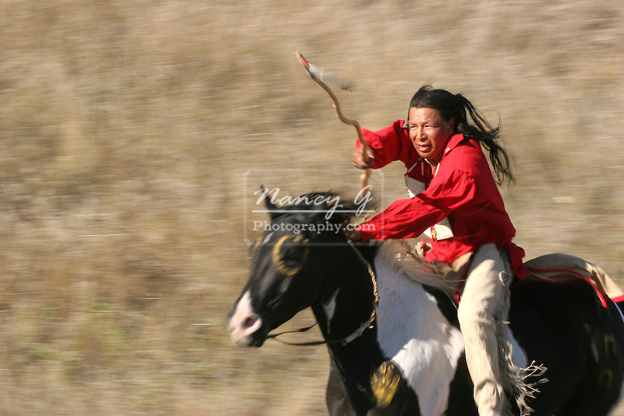 A Native American Sioux Indian man riding horseback on a Indian horse with a coup stick in the Plains of South Dakota