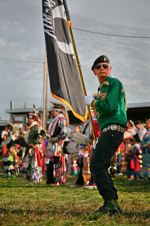 A veteran displaying the MIA flag exits the arena backwords at the end of the color guard at the conclusion to the Grand Entry.