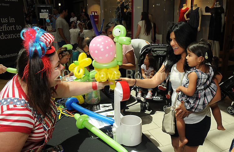 Suzzala gives a balloon to a child at the M.D. Anderson Back to School Fashion show at the Galleria Saturday Aug. 06,2016.(Dave Rossman Photo)
