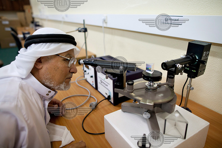 Lecturer of Physics, Mahmoud Abdel Rahman, using equipment in the Optics Laboratory, part of the Physics Department in the Islamic University.