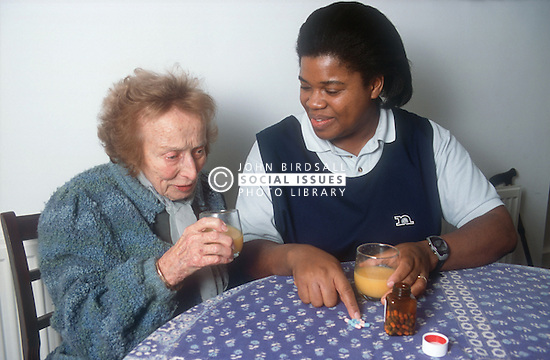 Carer explaining medication to elderly woman,