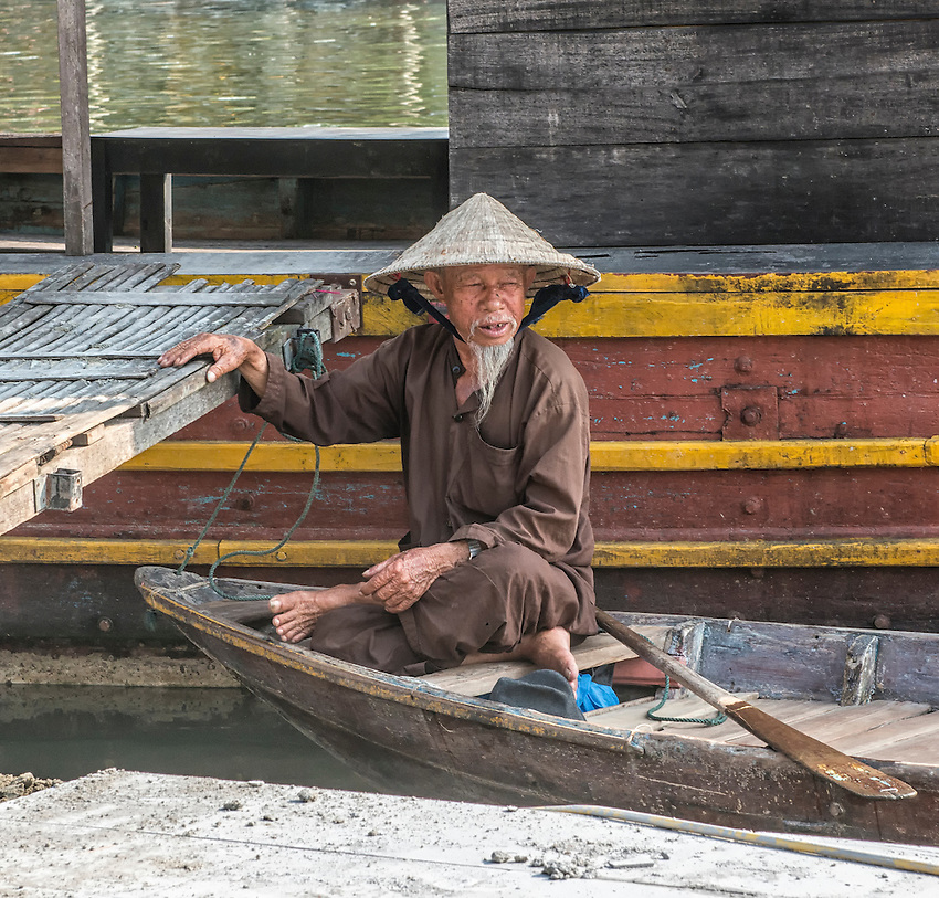 A boatman in Hoi An sits in his boat on the Thu Bon River and watches for customers.