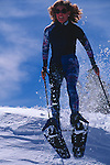 Woman jumping off a ledge in snowshoes