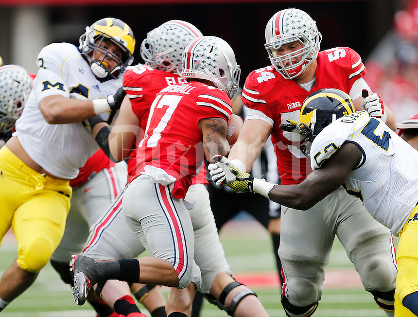 Ohio State Buckeyes offensive lineman Billy Price (54) blocks Michigan Wolverines defensive end Mario Ojemudia (53) to open a hole for Ohio State Buckeyes running back Jalin Marshall (17) during the college football game between the Ohio State Buckeyes and the Michigan Wolverines at Ohio Stadium in Columbus, Saturday morning, November 29, 2014. The Ohio State Buckeyes defeated the Michigan Wolverines 42 - 28. (The Columbus Dispatch / Eamon Queeney)