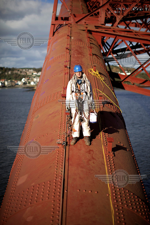 William Waddell, in full access gear, perpares to paint contact points on Inchgarvie on the 125 year old Forth Rail Bridge which spans the river Forth near Edinburgh. Network Rail, the operator of the rail track that leads over the bridge, has spent 10 years and GBP 130 million repainting the 230,000 square metres of steel and 6.5 million rivets on the bridge. The iconic red paint used on the bridge is made to match the red-oxide paint used over 100 years ago. The bridge will now need no further painting for at least 20 years.