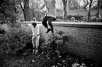 CZECH REPUBLIC / Prague / Zizkov district August 1998..Teenagers jump a wall lining a cemetary in this working class area of Prague...© Davin Ellicson / Anzenberger