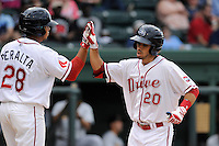Third baseman Carlos Asuaje (20) of the Greenville Drive is congratulated by Aneudis Peralta after scoring a run in a game against the Charleston RiverDogs on Wednesday, June 11, 2014, at Fluor Field at the West End in Greenville, South Carolina. Greenville won, 6-3. (Tom Priddy/Four Seam Images)