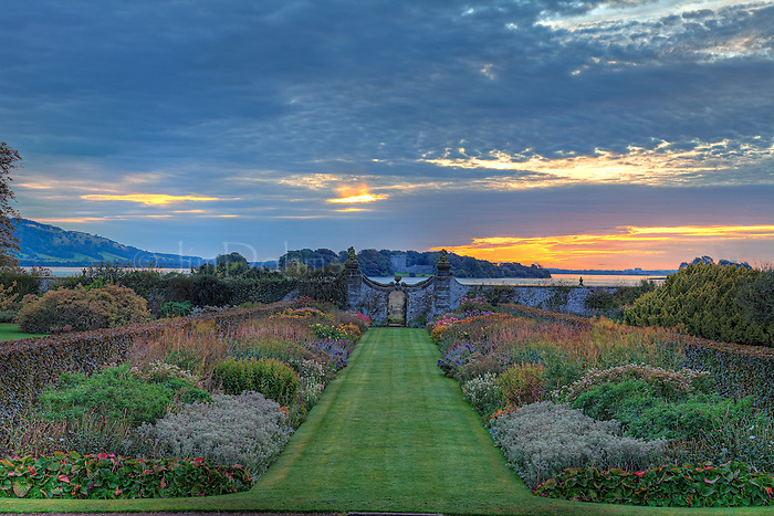 """The Kinross House is located north of Edinburgh on the western shore of Loch Leven. Looking beyond """"The Fish Gate"""" you can see Lochleven Castle. Even in early October flowers are in bloom and the grass feels like fine carpet."""