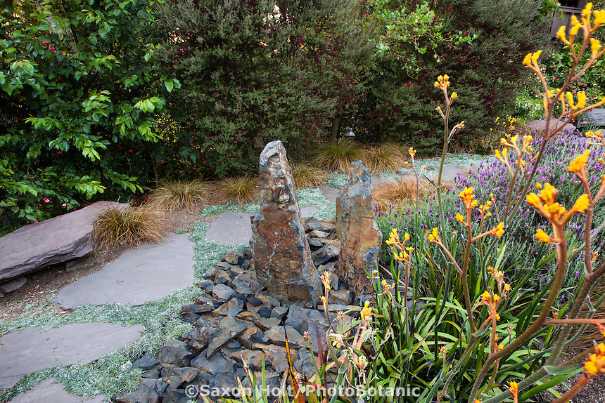 Stone, rock focal point by stepping stone path and perennial border in drought tolerant California backyard garden; Roth-Epstein garden