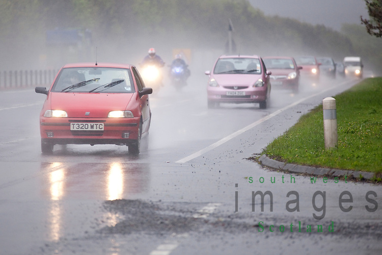 Dual carriageway road A75 near Dumfries Scotland UK bad weather rain mist spray motorcycles overtaking a line of cars