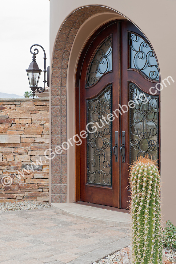 Massive wrought iron embellished glass double doors lead to luxury home