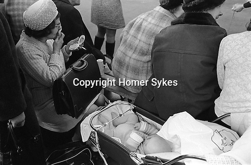 Middle aged woman putting on her make up with her baby in a pram at the Crufts Dog Show Olympia London England 1970
