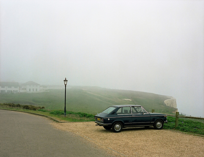 A solitary car parked near cliffs on the Sussex coast on a misty day.