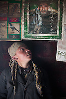 Mujaheed, son of the late Khan, look at President Karzai's poster..In and around the campment of Kyzyl Qorum, campment of the former deceased Khan, Abdul Rashid Khan..Trekking with yak caravan through the Little Pamir where the Afghan Kyrgyz community live all year, on the borders of China, Tajikistan and Pakistan.