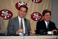 SANTA CLARA, CA: New San Francisco 49ers head football coach Steve Mariucci (left) is introduced to the media at a press conference in Santa Clara, CA in 1996 as club president Carmen Policy looks on. Photo by Brad Mangin