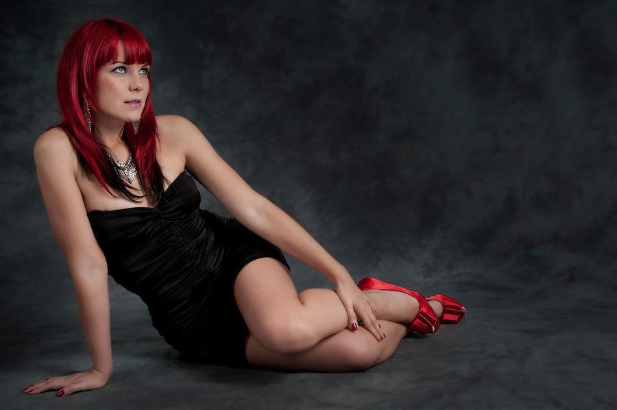 Young and sensual caucasian woman looking up seated in the floor.