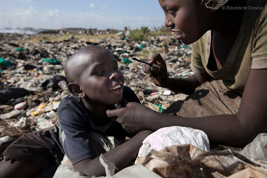 13 february 2013 - Dandora dumpsite, Nairobi, Kenya - A Kenyan girl puts on some make-up on a young boy at the Dandora dumpsite, one of the largest and most toxic in Africa. Located near slums in the east of the Kenyan capital Nairobi, the open dump site was created in 1975 and covers 30 acres. The site receives 2,000 tonnes of unfiltered garbage daily, including hazardous chemical and hospital wastes. It is a source of survival for many people living in the surrounding slums, however it also harms children and adults' health in the area and pollutes the Kenyan capital. Photo credit: Benedicte Desrus