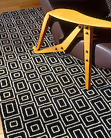 Detail of a contemporary geometric rug and retro armchair