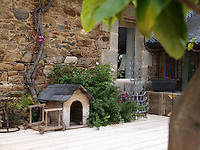 A rustic dog kennel sits against the stone wall of the cottage on an area of wooden decking