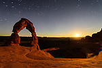 The Delicate Arch in Arches National Park near Moab, Utah as seen by the light of a setting moon.