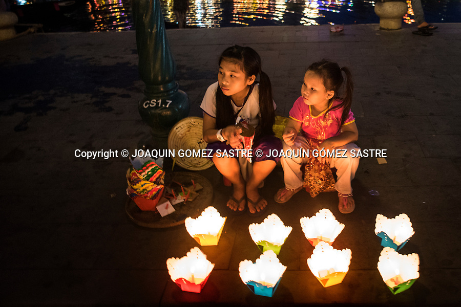 Two girls sell candles at dusk on the banks of the Thu Bon River in Hoian city (Vietnam)<br /> HOIAN-VIETNAM