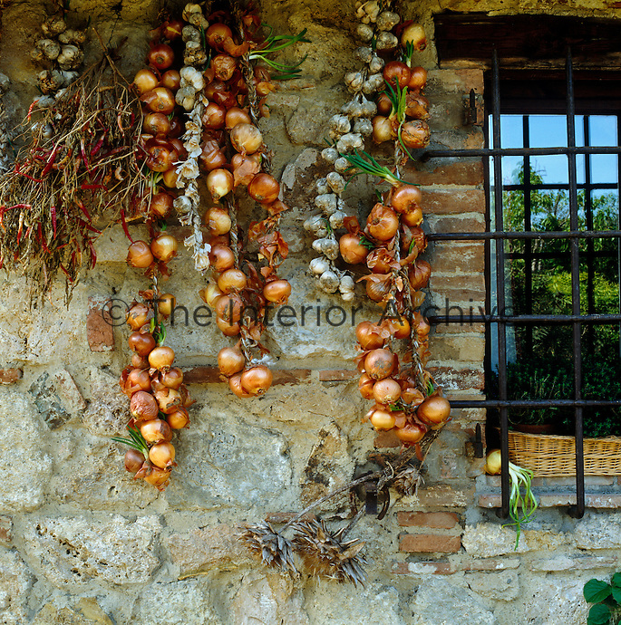 Strings of onions hang drying in the shade against the stone wall of the house