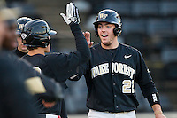 Will Craig (22) of the Wake Forest Demon Deacons is greeted by teammates after scoring a run against the Georgetown Hoyas at Wake Forest Baseball Park on February 16, 2014 in Winston-Salem, North Carolina.  The Demon Deacons defeated the Hoyas 3-2.  (Brian Westerholt/Four Seam Images)