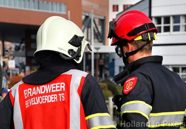 Overleg tussen de Brandweer bevelvoerder en een andere brandweerman. Brandweer demonstratie tijdens Alkmaar Ontzet op 8 oktober