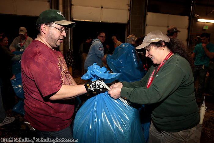 Chris Blankenship, left, and Denise Ronek zip-tie one of the 1500 bags of straw at Airland Transport in Anchorage to be sent out to the 22 checkpoints along the Iditarod trail Thursday, Feb. 7, 2013.