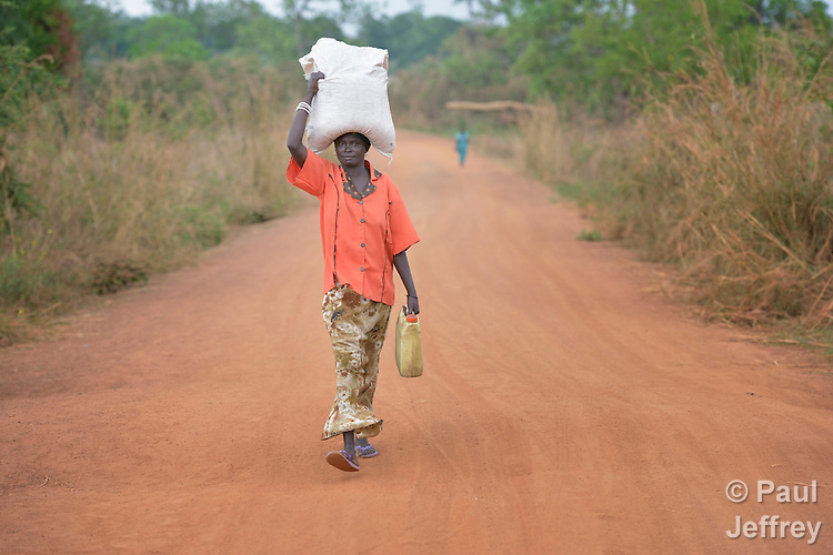 Asanta Jantana walks along a road in Kotobi, South Sudan, carrying some of the food and non-food items she received during a distribution of aid to displaced families. She is one of thousands who were displaced by political violence that broke out in December 2013 and quickly fractured regions of the young nation along ethnic and tribal lines. Jantana fled Juba with her seven children for this village, where she moved in with a brother. Yet she hasn't had enough food for her whole family, so she sent four of her children to live with another relative. She hasn't heard from her husband, a soldier, since the fighting began. Finn Church Aid, a member of the ACT Alliance, provided materials for this aid distribution. The ACT Alliance is providing a variety of services to internally displaced families throughout the country.