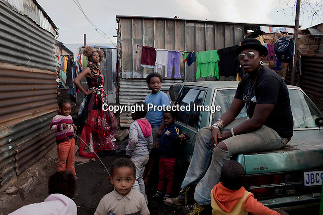 SOWETO, SOUTH AFRICA: Designers Sibu FDB, age 29, with a model and one of his dresses during a shoot in a poor area in Kliptown, Soweto, South Africa. Soweto is South Africa's largest township and it was founded about one hundred years to make housing available for black people south west of downtown Johannesburg. The estimated population is between 2-3 million. Many key events during the Apartheid struggle unfolded here, and the most known is the student uprisings in June 1976, where thousands of students took to the streets to protest after being forced to study the Afrikaans language at school. Soweto today is a mix of old housing and newly constructed townhouses. A new hungry black middle-class is growing steadily. Many residents work in Johannesburg, but the last years many shopping malls have been built, and people are starting to spend their money in Soweto.  (Photo by Per-Anders Pettersson)