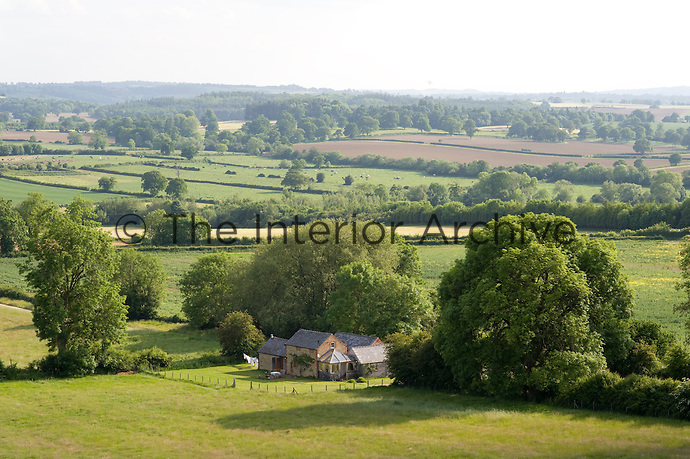 The property nestles is sheltered by a grove of trees with the rolling English countryside beyond